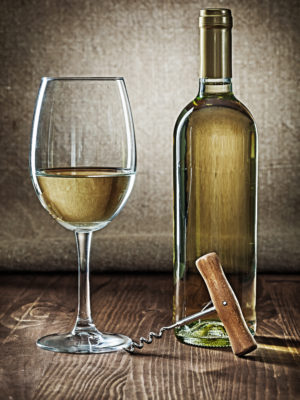 bottle and glass with white wine and corcksrew