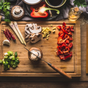 Copped vegetables ingredients for tasty vegetarian stir fry dishes on wooden cutting board with knife and chopsticks, top view. Asian cuisine. Healthy eating and food concept