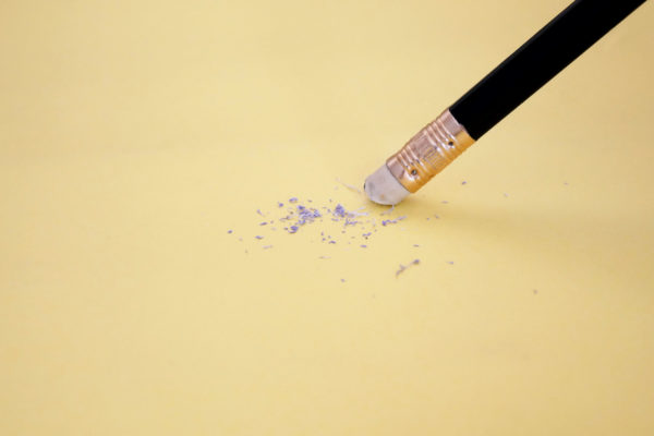 Pencil eraser removing a written mistake on a piece of paper, delete, correct, and mistake concept.