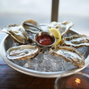 Bowl of raw oysters on ice with sauce and lemon.