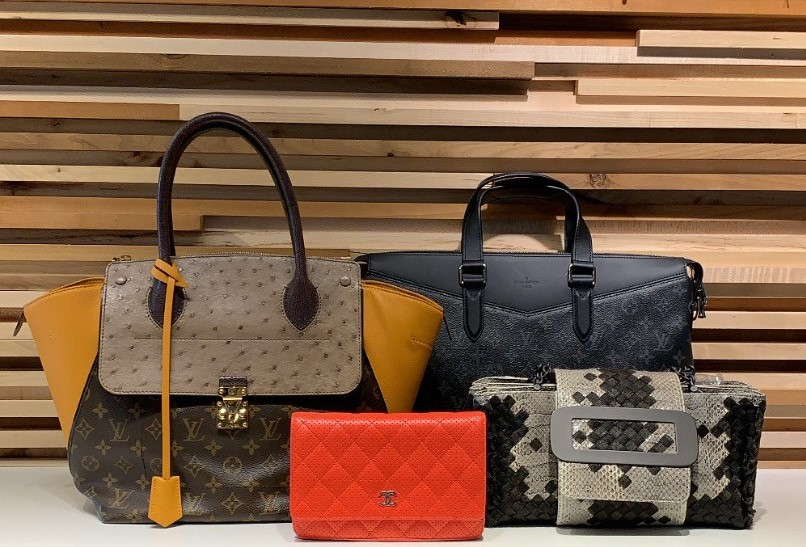 Four handbags in front of a wooden wall. Two large handbags in the back, one is brown and tan and the other is black. A small red clutch is in the front next to a snake skin clutch.