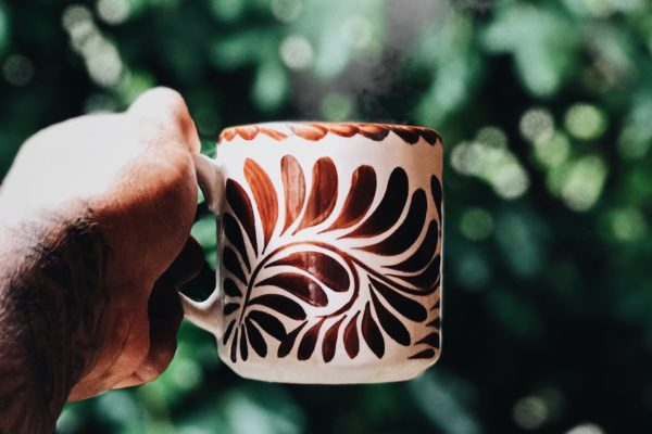 A hand holds an intricately designed coffee mug
