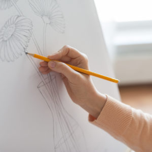 art, creativity and people concept - artist hands with graphite pencil drawing still life picture of flower in vase on paper at studio