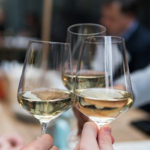Three glasses of white wine are clinking together