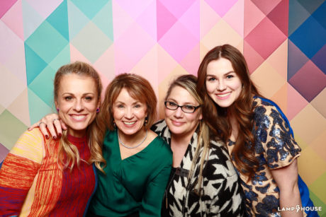 a group of four women pose together at the holiday tables event