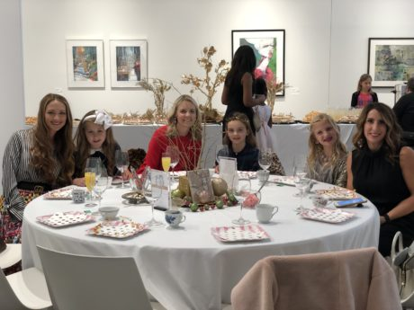 a group of women and young girls sit at a holiday table