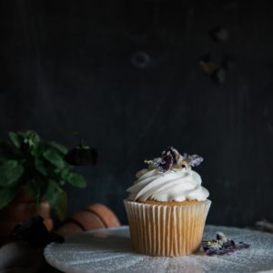 A single vanilla cupcake sits on a cake stand