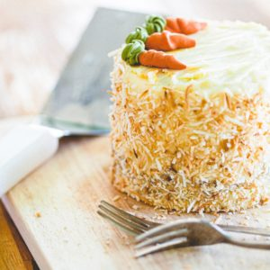 a carrot cake sits on a cutting board