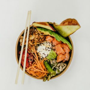 a bowl of asian food with chopsticks